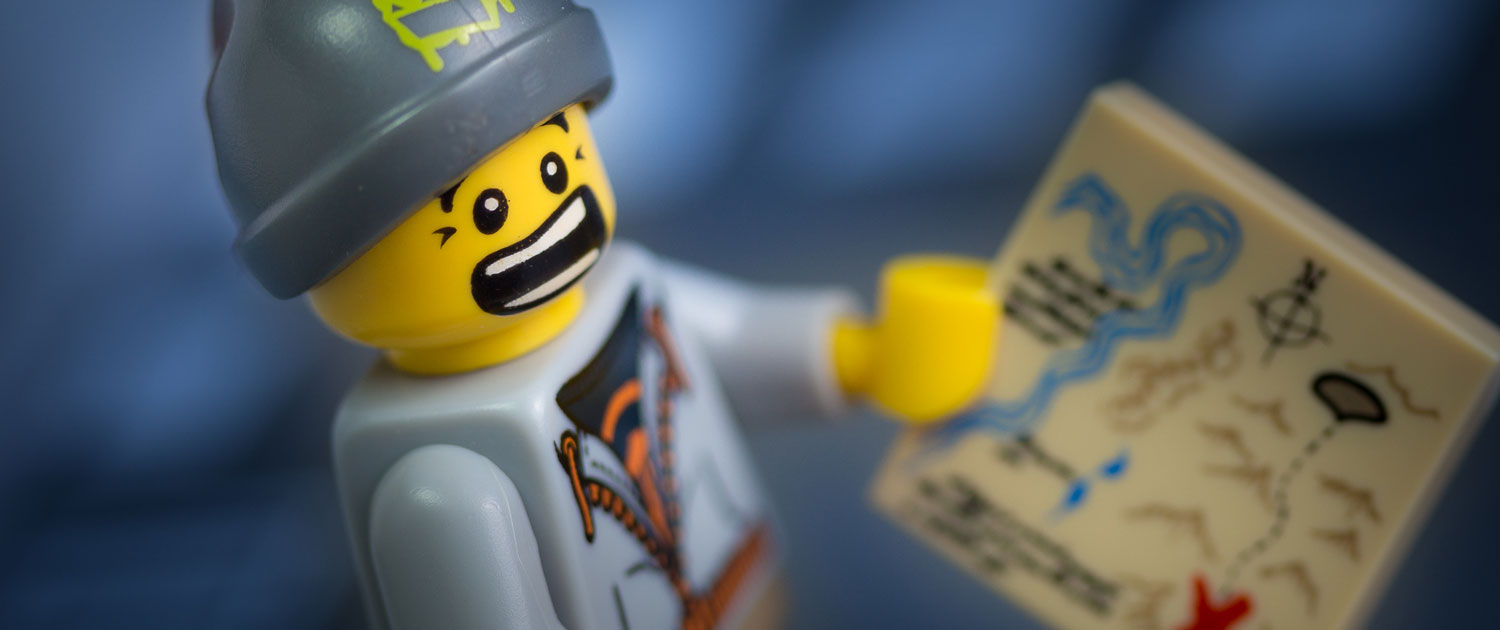 Photograph of a LEGO minifigure holding a map and looking worried