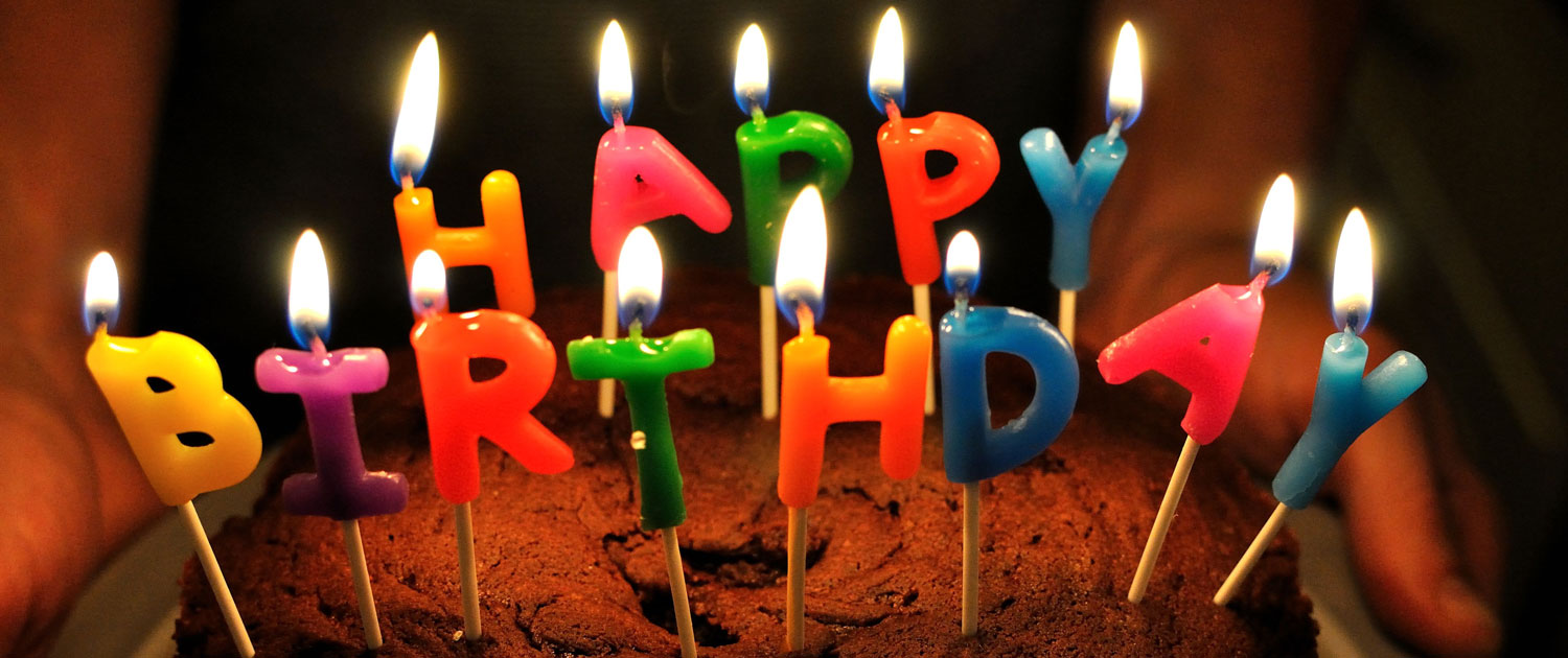 """A birthday cake with candles spelling """"Happy Birthday"""""""